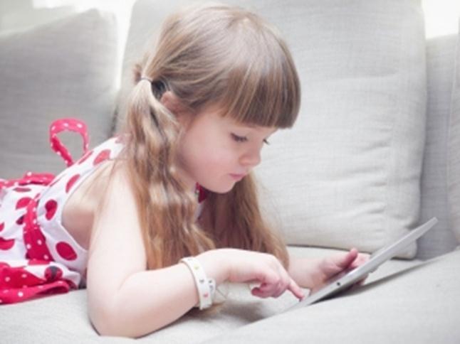 Девочка играет на планшете